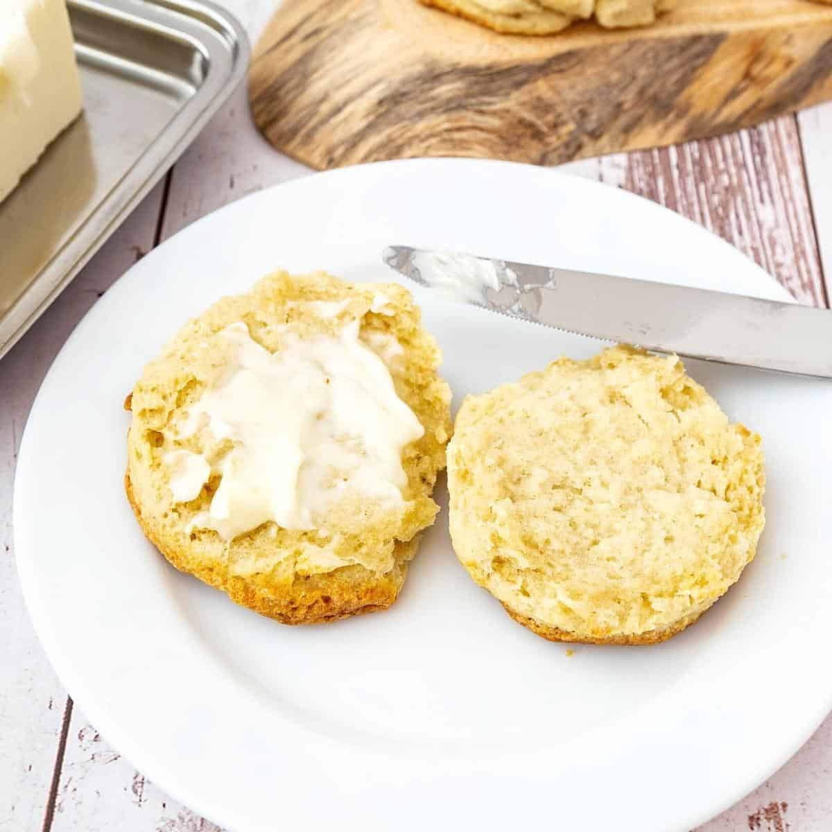 A sliced biscuit with butter on a plate.