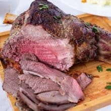 A wooden platter with sliced leg of lamb.