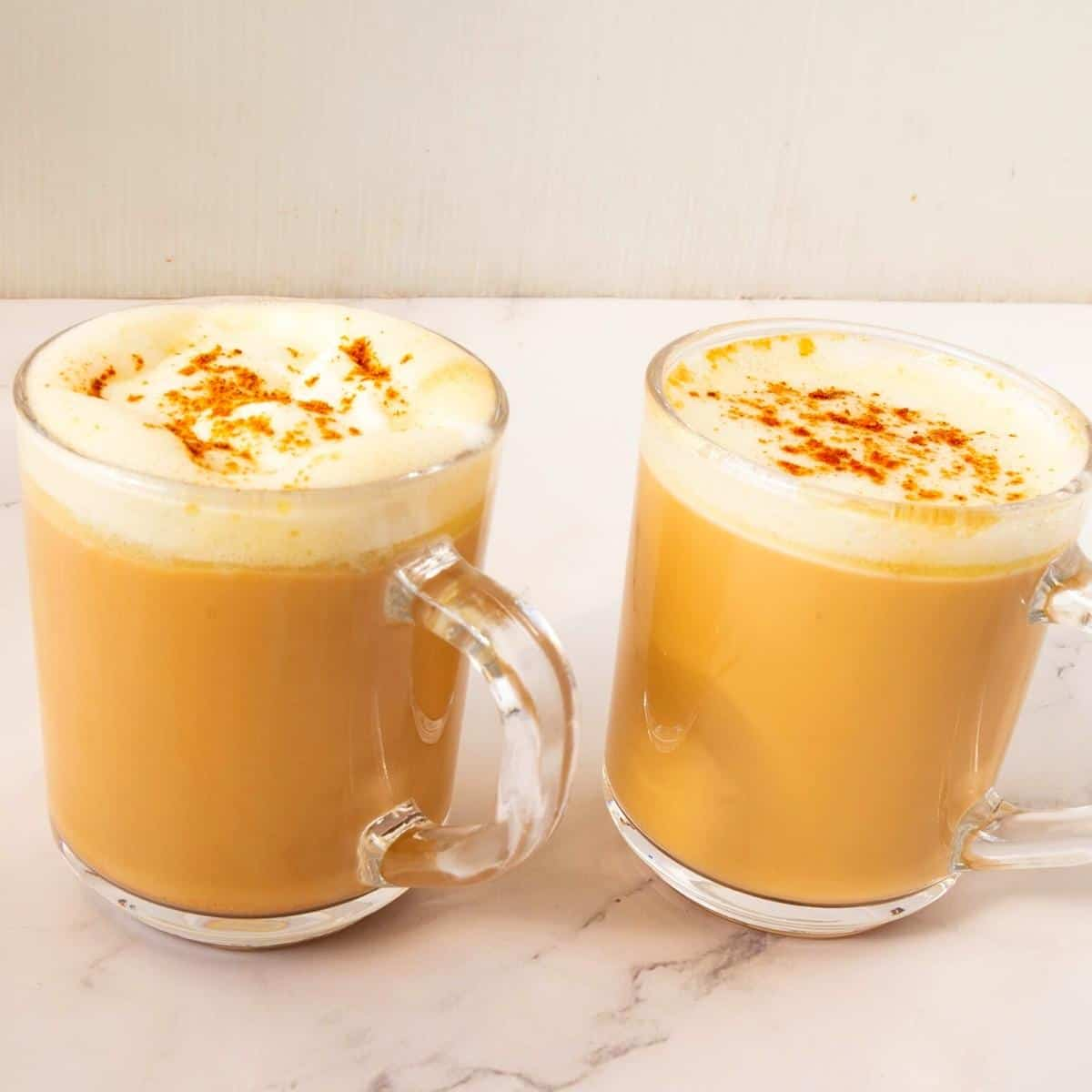 Two cups with latte using chai spice.