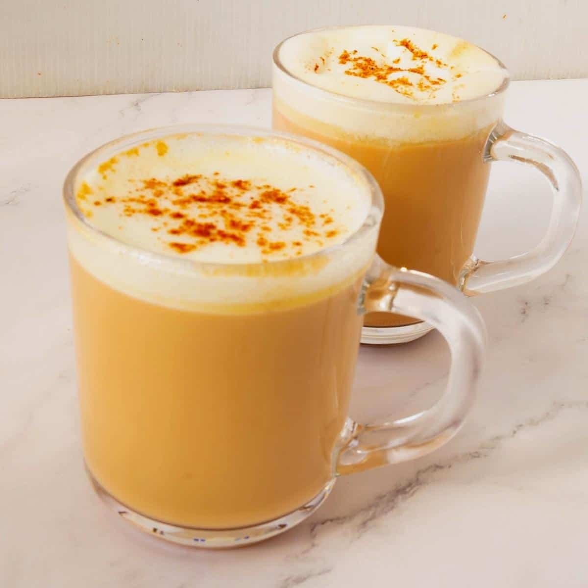 Two cups with chai tea latte.