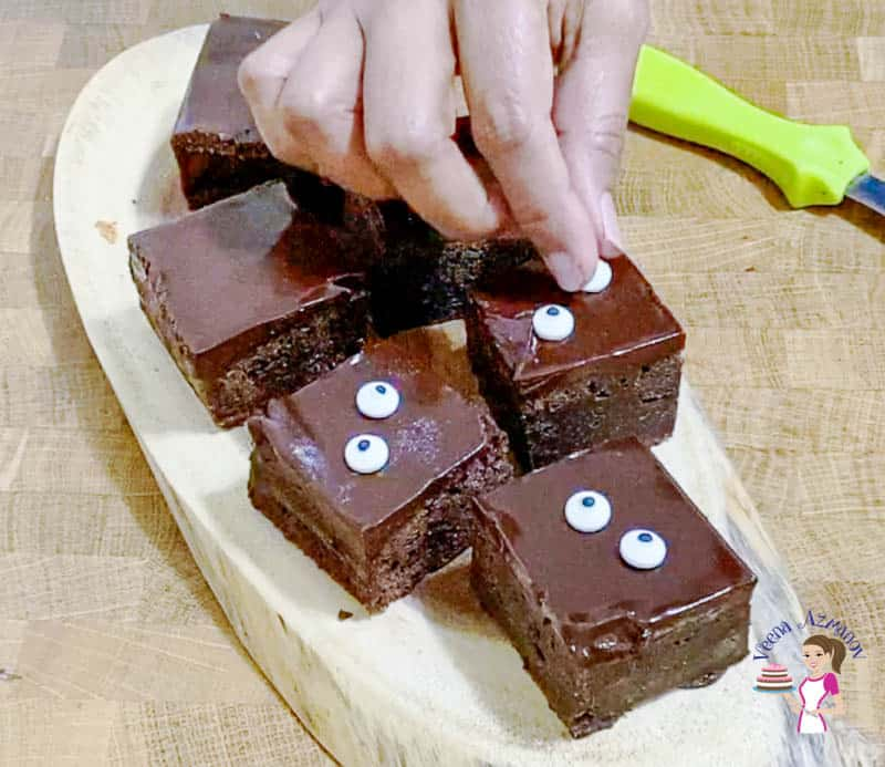Adding eyes to the brownies for Halloween