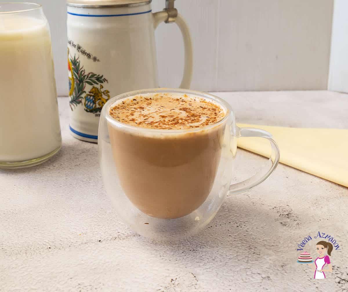 A pumpkin latte in a glass cup