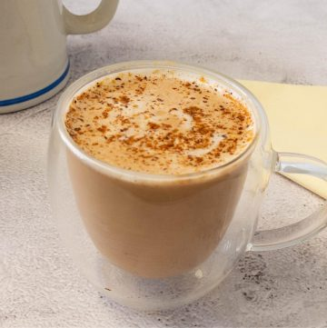 A chai latte in a glass cup on a marble surface