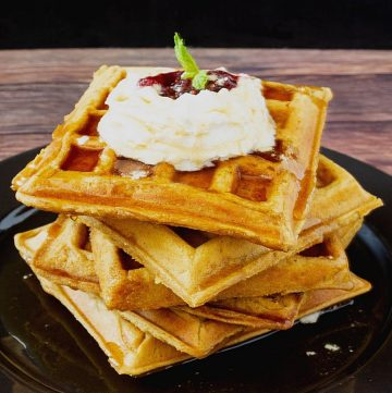 Waffles on a black plate with whipped cream.