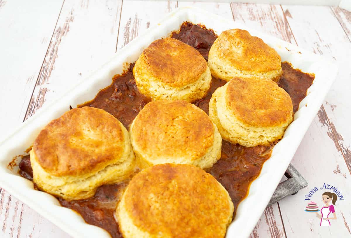 A baking dish with lamb and biscuits