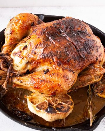 A cast iron skillet with whole roasted chicken.