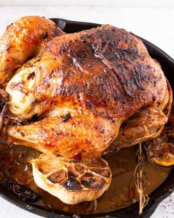 A cast iron skillet with roasted chicken