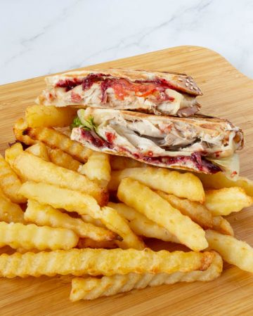 Two half sandwiches on a wooden board with fries