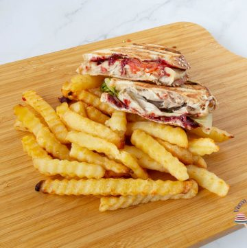 A wooden board with sandwich and fries