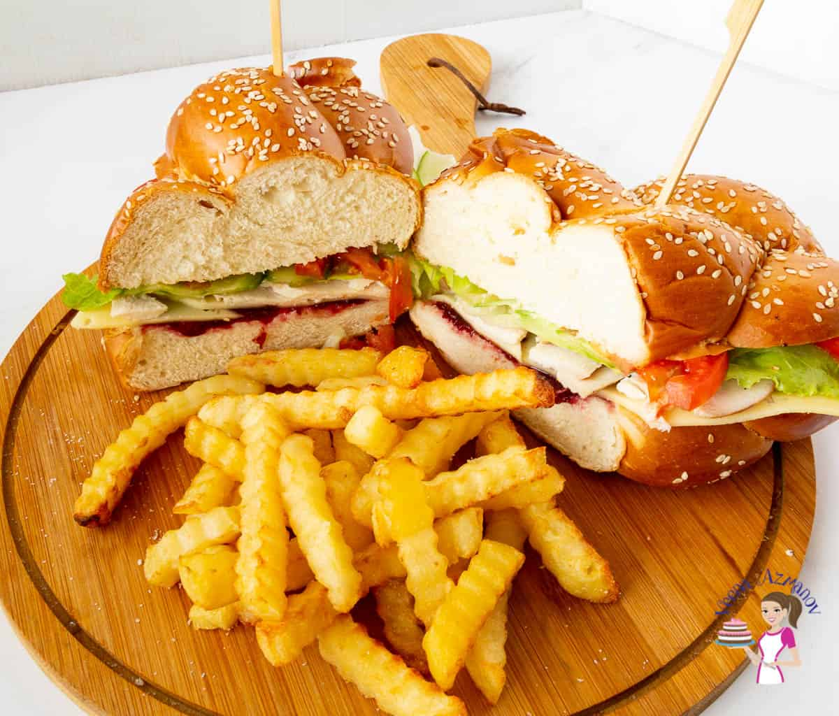 A cut sandwich with fries on a wooden board