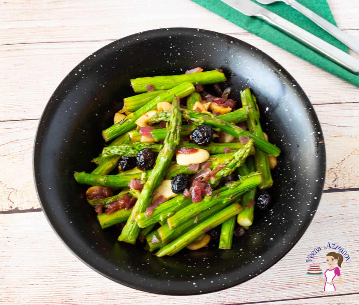 a black bowl with sautéed asparagus