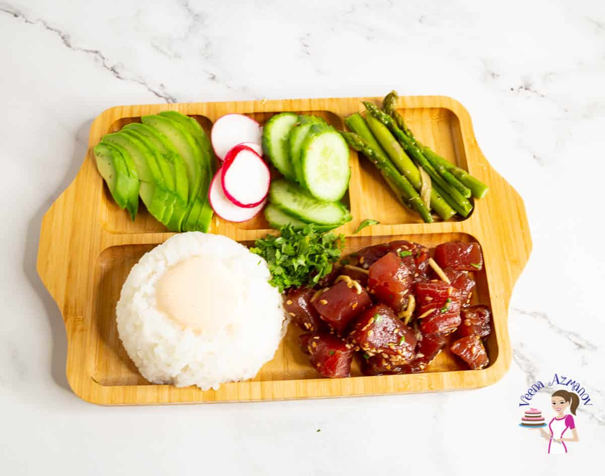 A wooden plate with ahi tuna, rice and veggies