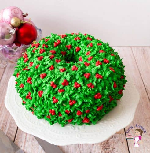 A frosted cake with holly leaves and berries on a cake stand