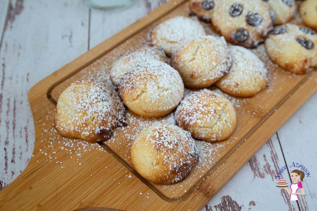 A wooden board with cookies dusted in powdered sugar