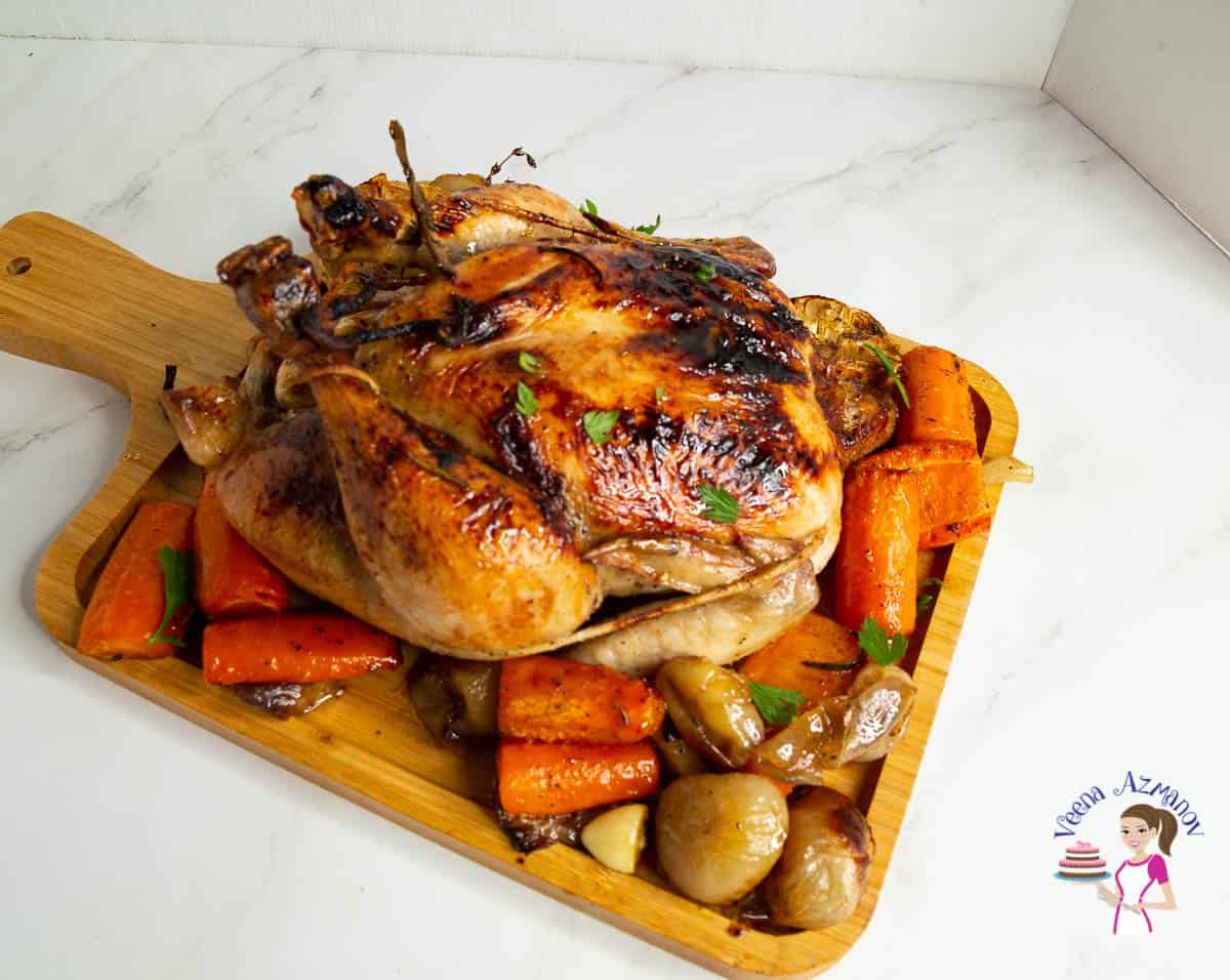 A wooden tray with roasted chicken and veggies