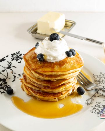 A stack of pancakes with whipped cream and blueberries