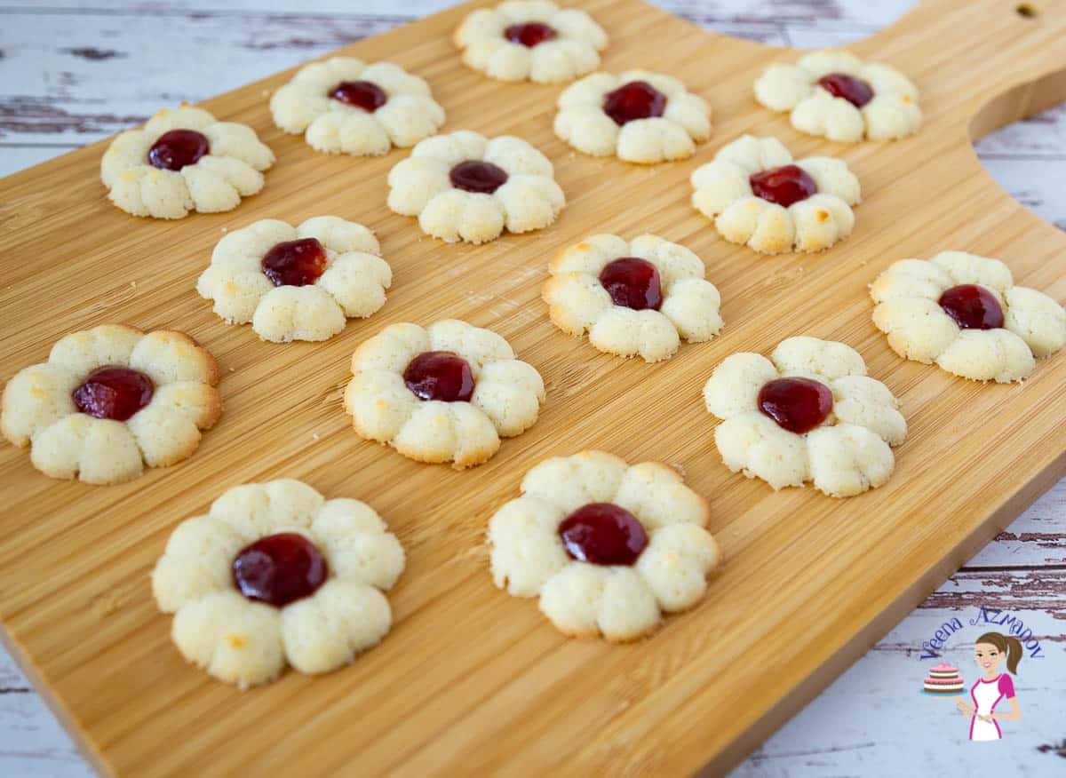 A wooden board with jam spritz cookies