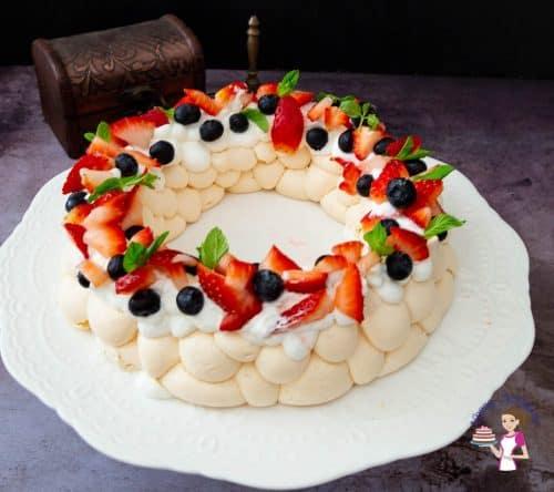 A pavlova wreath on a cake stand