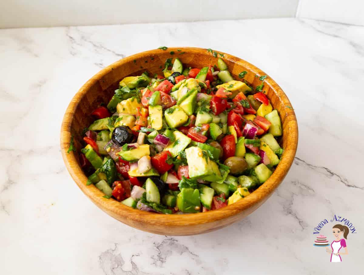 A wooden salad bowl with avocado salad