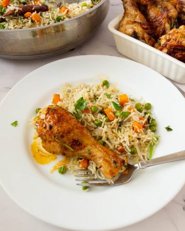 A baked chicken drumstick on rice pilaf