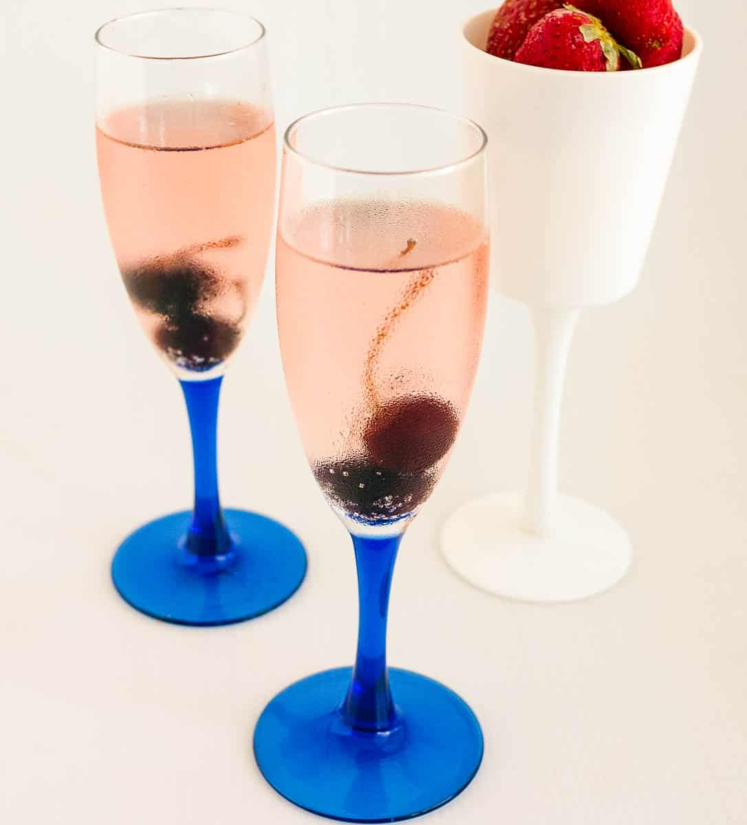 Cherry champagne cocktail in a champagne glass
