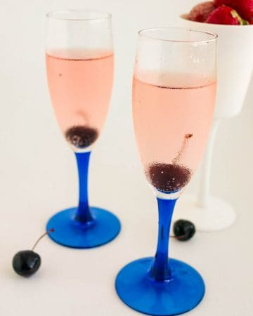 Two champagne glasses with champagne cocktail