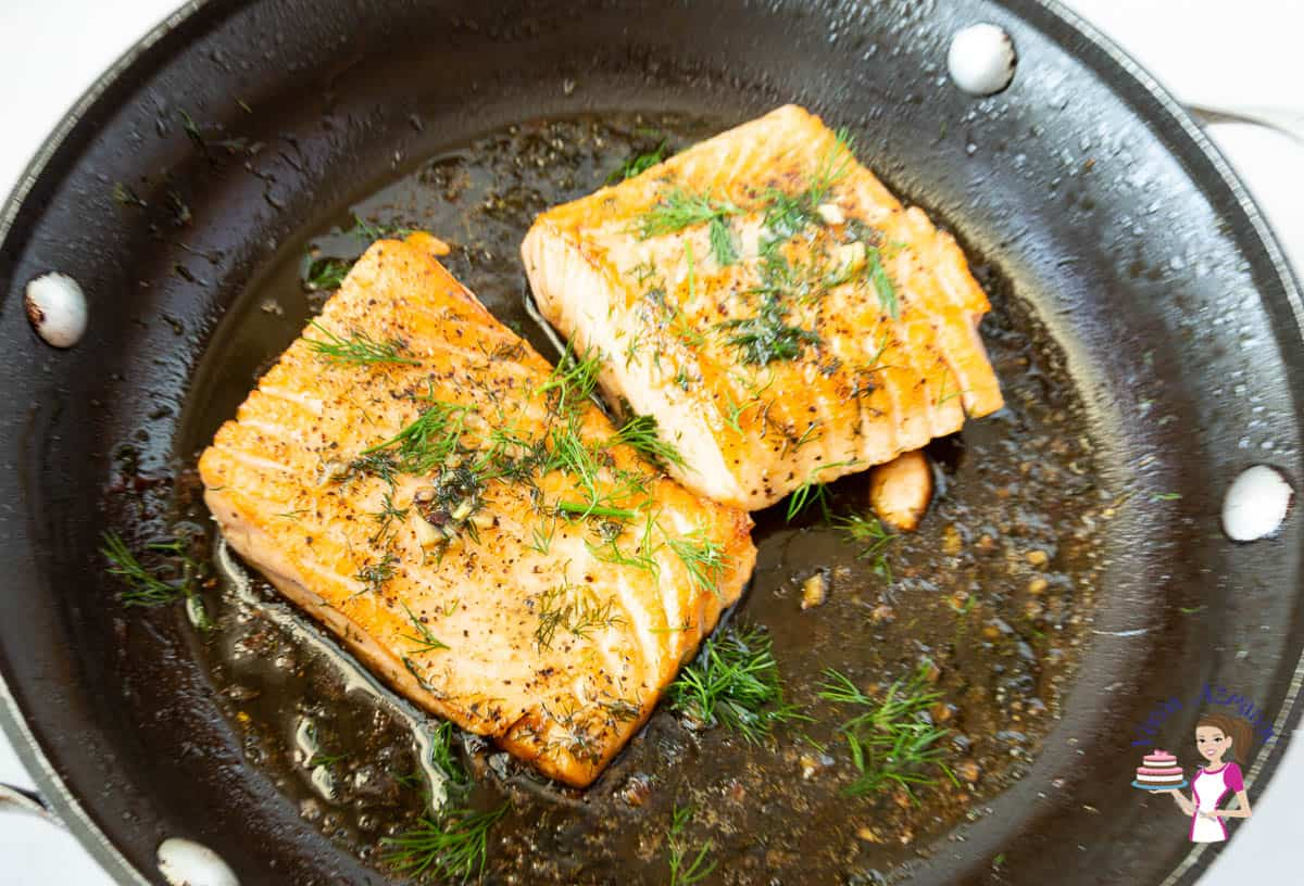 Two pieces of pan fried salmon in a skillet