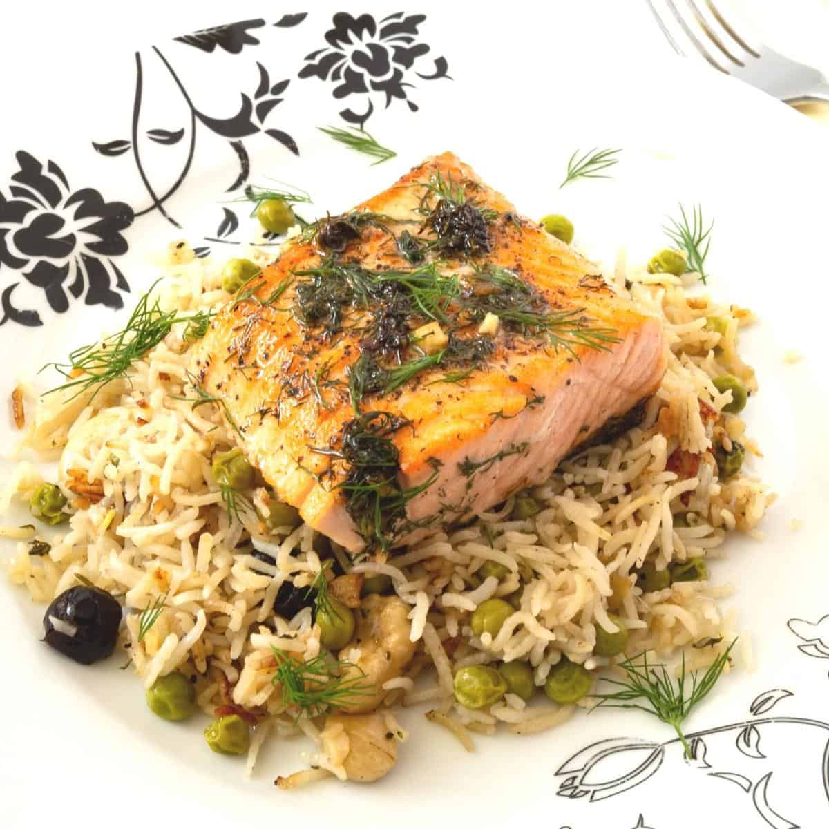 A white plate with basmati rice and salmon fillet.