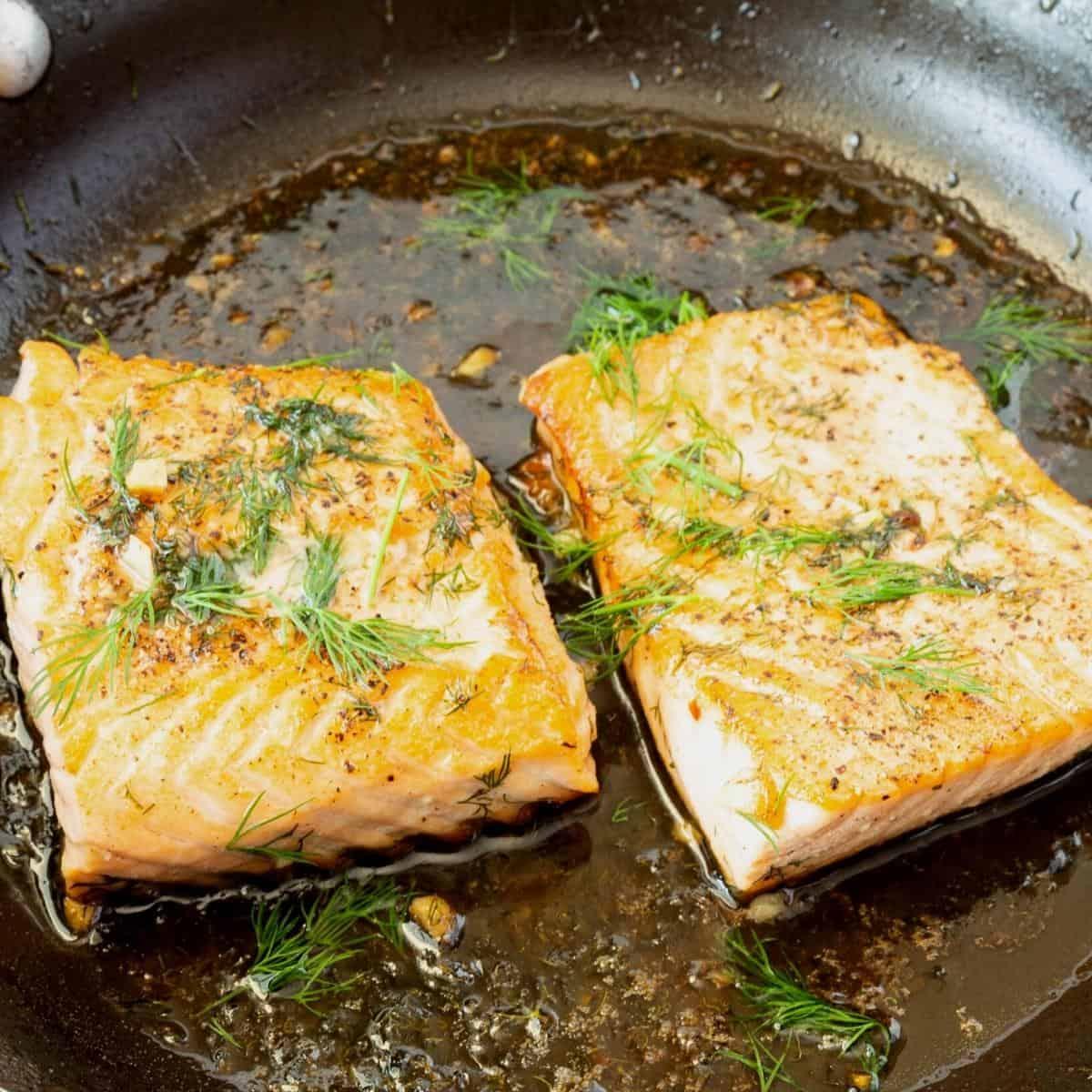 A saute pan with sautéed salmon.
