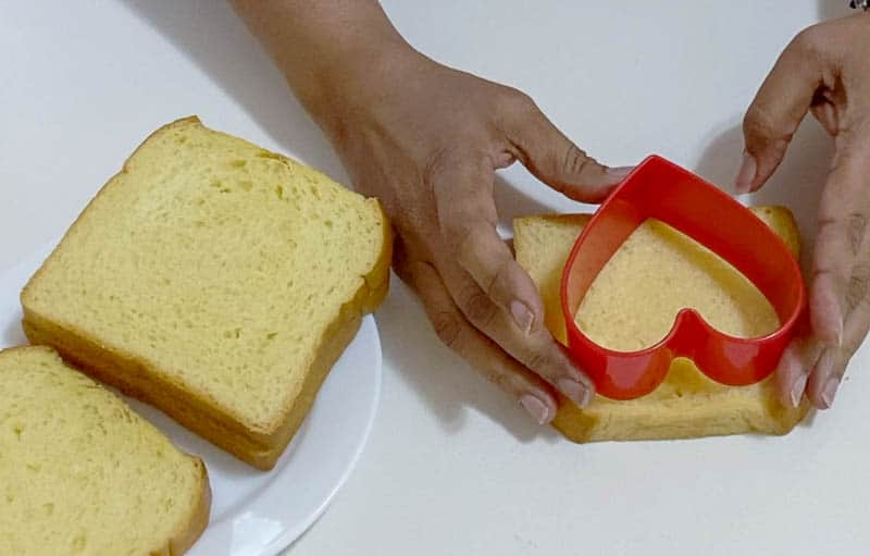 Cutting the heart shape from the bread