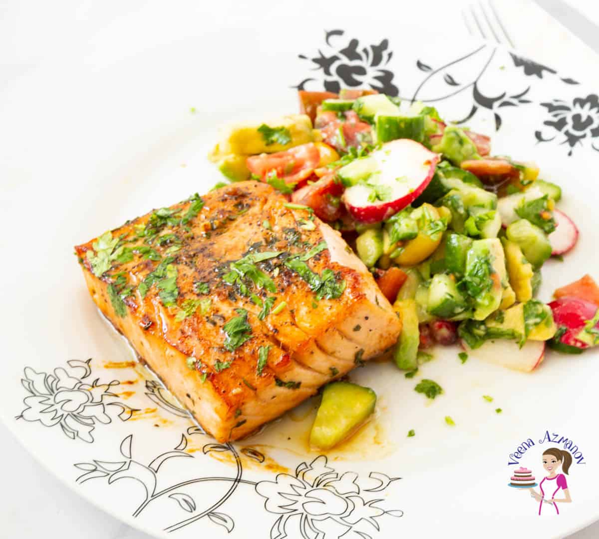 A white plate with salmon and avocado plate