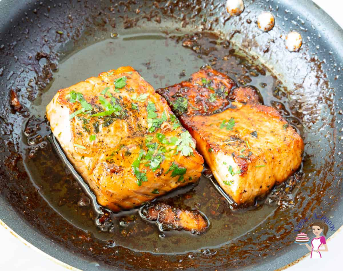 A skillet with two pieces of salmon
