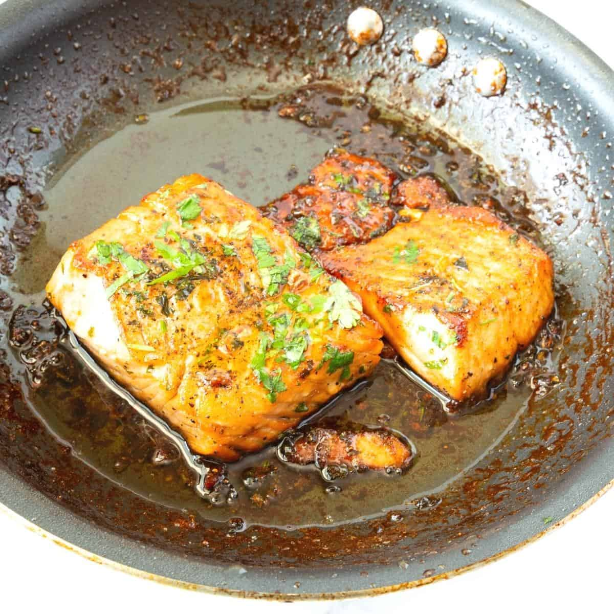 A skillet with salmon pan fried with honey garlic butter.