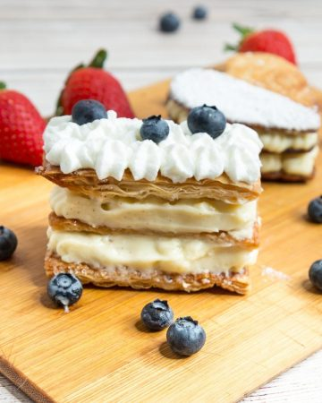 A wooden board with napoleaon puff pastry dessert blueberries and strawberries