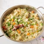 A saute pan with pilaf and veggies