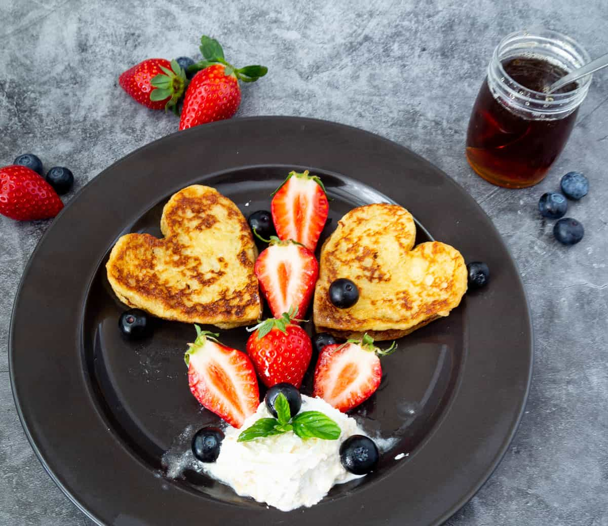Heart shaped French toast on a black plate