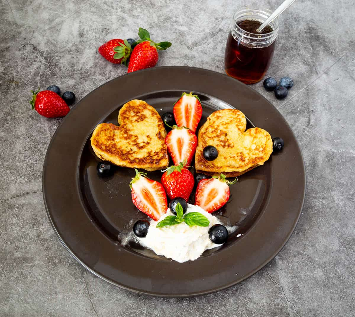 black plate with french toast and fruits
