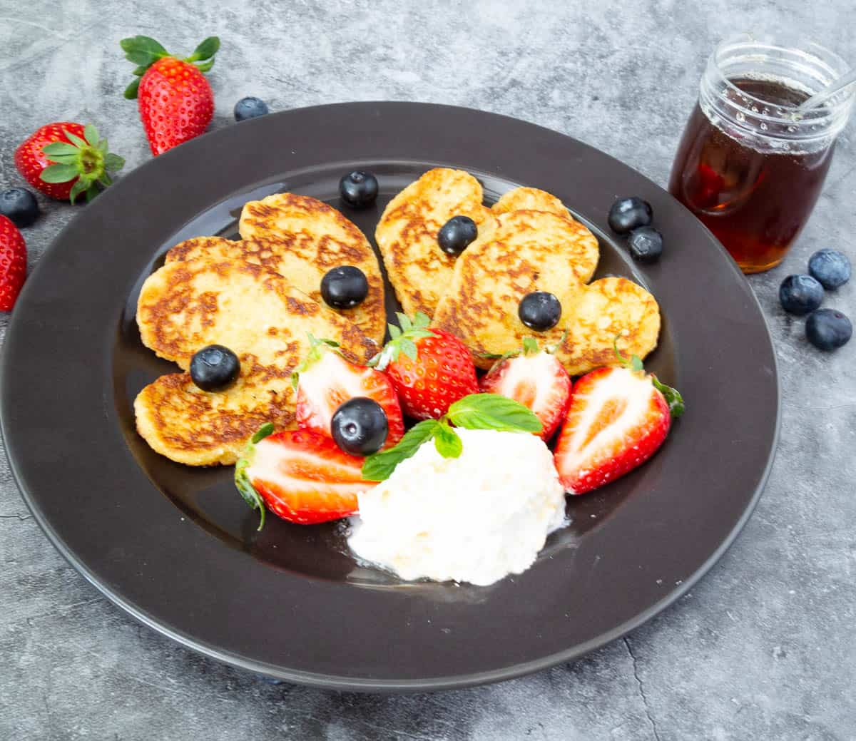 French toast and fruits on a black plate