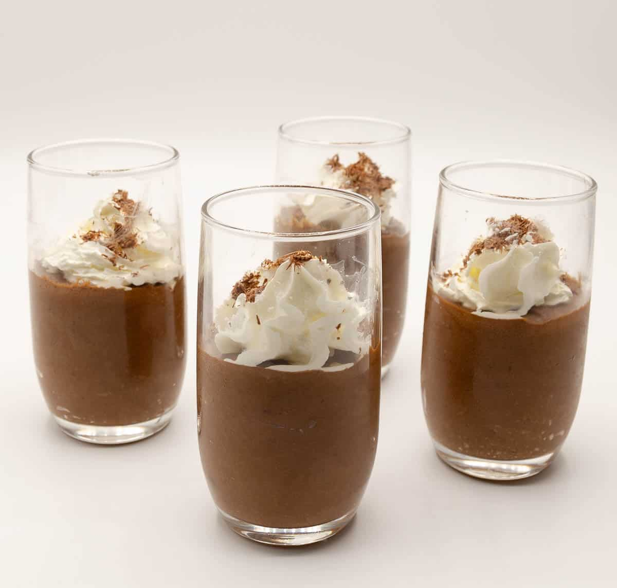 4 glasses of chocolate mousse with whipped cream