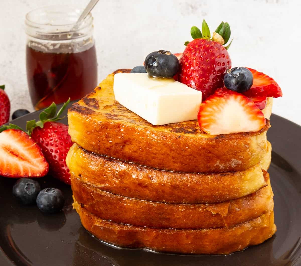 Stack of French toast on a plate with butter and fresh fruits