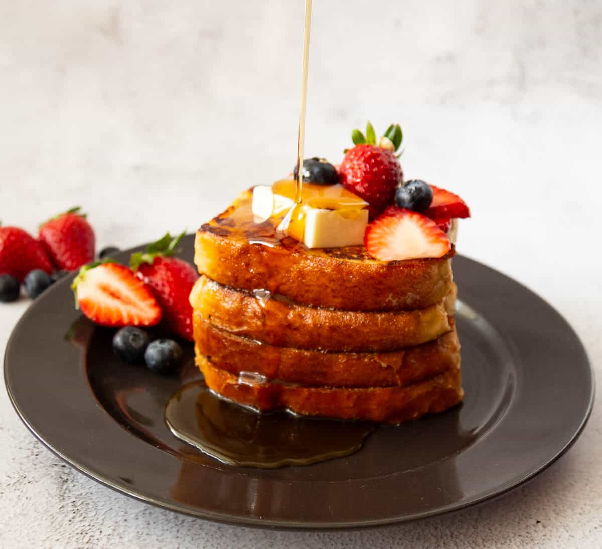 Stack of French toast on a black plate