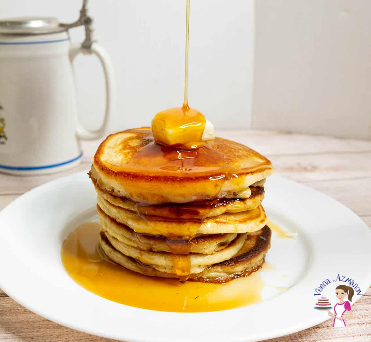 A stack of pancakes in a plate with butter and honey