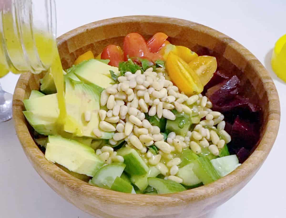 Pouring salad over salad in a bowl