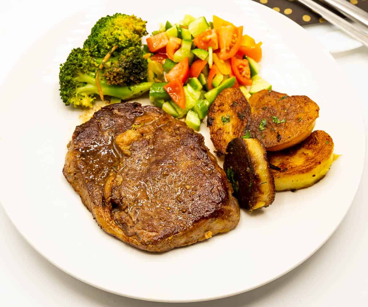 Cooked steak, potatoes and veggies on a plate