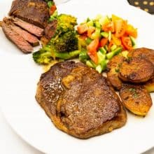 A plate with cooked steak potatoes and salad