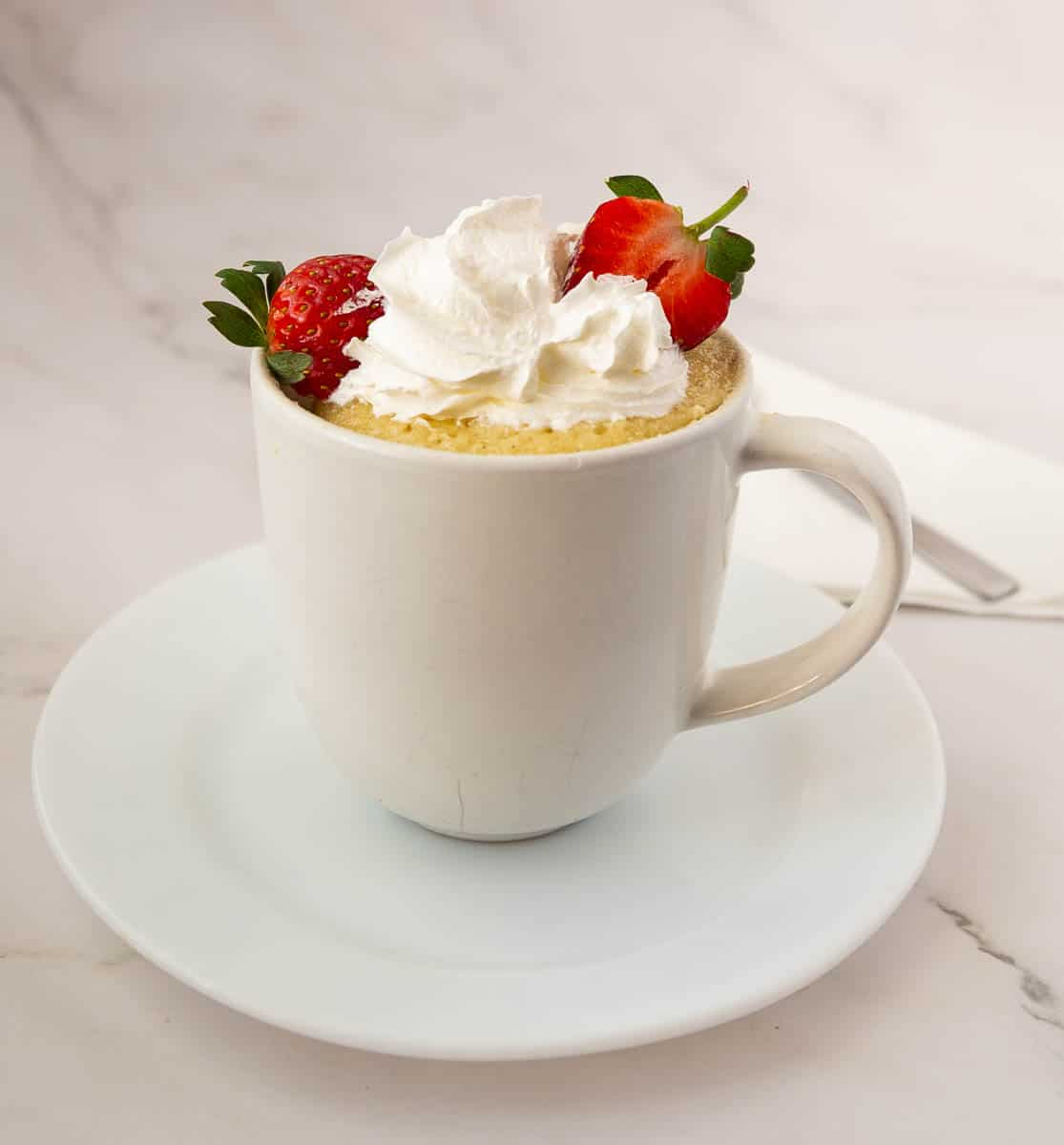 Vanilla cake in a mug topped with whipped cream