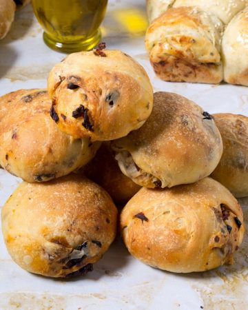 Olive rolls on a table with sun dried tomatoes.