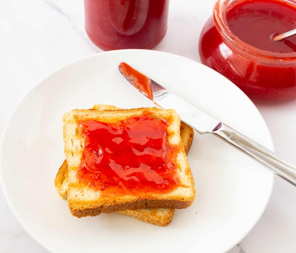 A slice of toast with jelly on a plate.