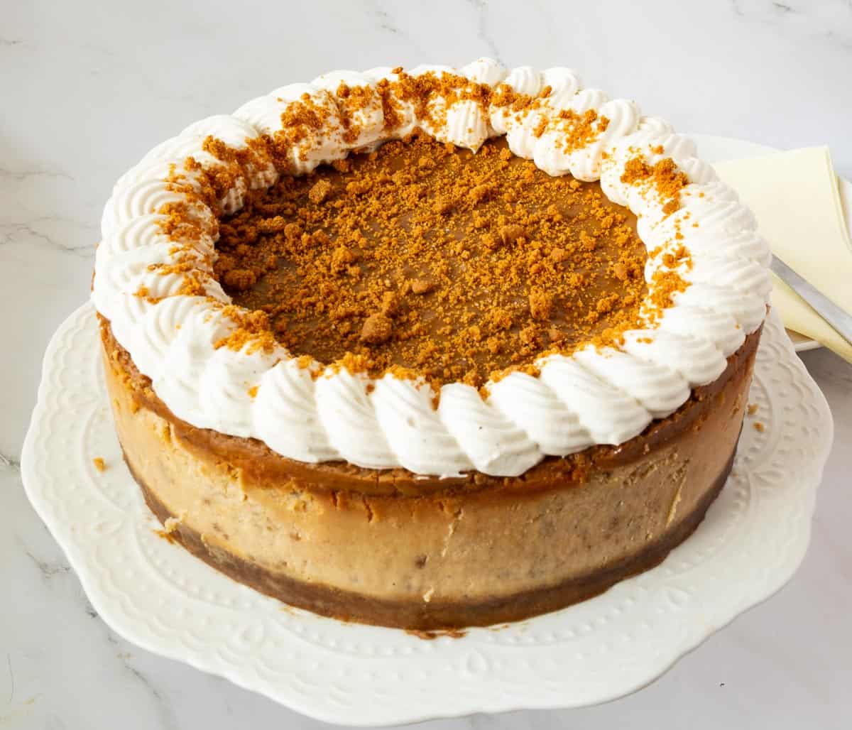 A full baked cheesecake with biscoff glaze on a cake stand.