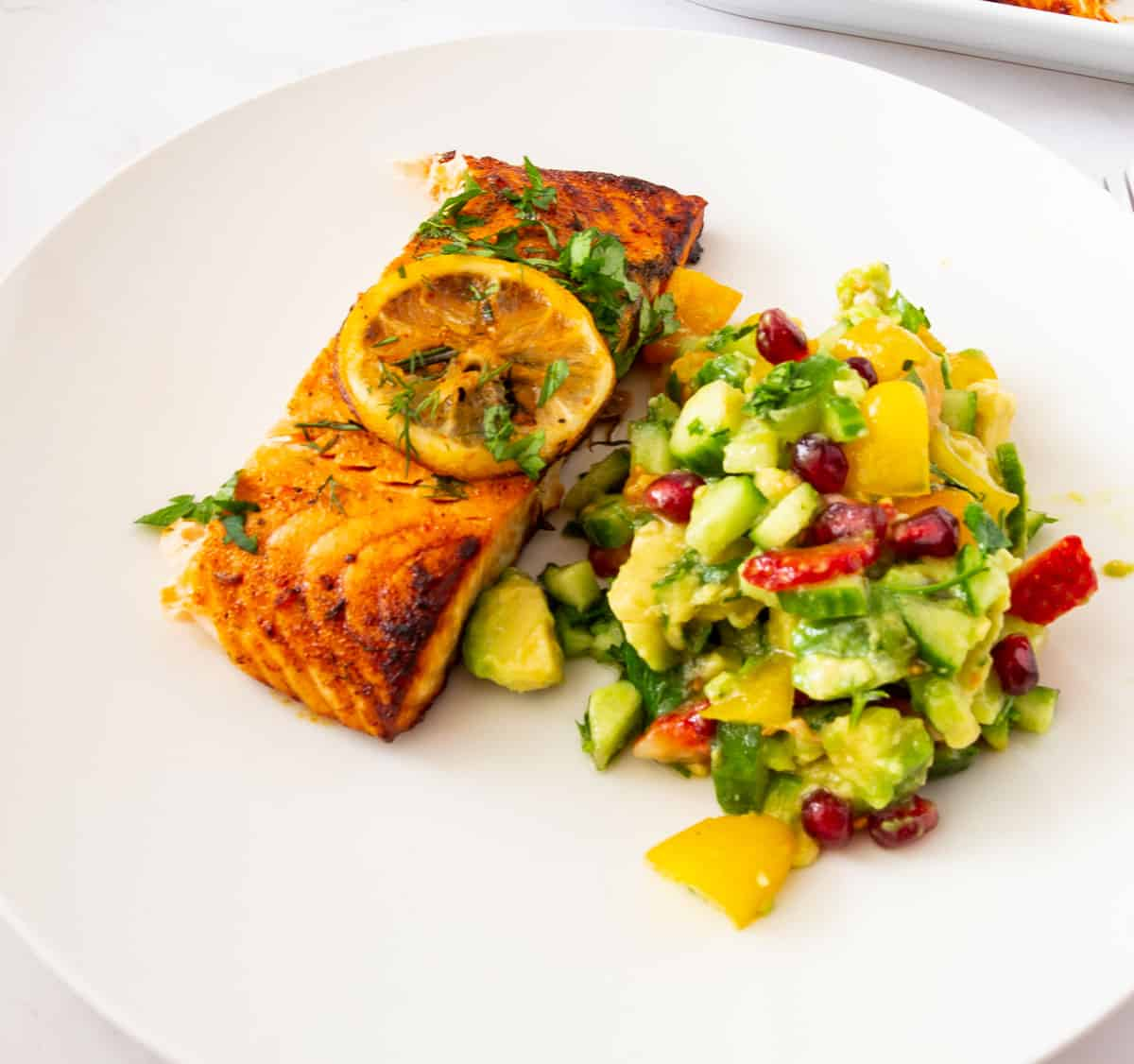 A white plate with salmon and avocado salad.